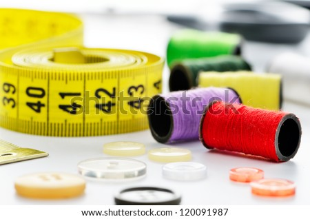 Sewing accessories: tape measure, buttons, spool and scissors