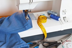 Sewing and needlework at home. Stitching jeans on a sewing machine. Processing the bottom of denim pants. Sewing accessories: scissors, pins, spools of thread, measuring tape, and a bobbin on desktop