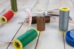 Sewing background. Accessories for needlework on wooden background. Spools of thread, scissors, measuring tape, sewing supplies. Set for needlework top view