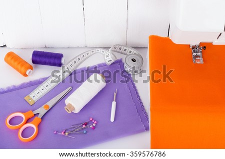 Sewing background concept. Sewing machine with sewing utensils for needlework - cotton fabric, spools of thread, scissors, measuring tape on white wooden background #359576786