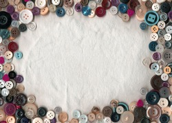 Sewing color buttons frame on fabric texture background. Collection of assorted spare clothes buttons vintage. Sewing tools close up.