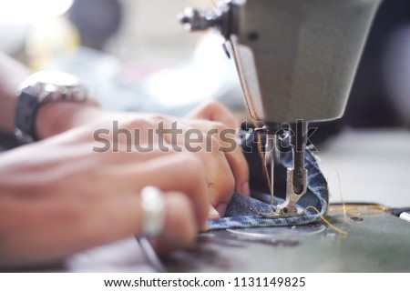 Sewing denim jeans with sewing machine. Repair jeans by sewing machine. Alteration jeans, hemming a pair of jeans, handmade garment industrial concept. #1131149825