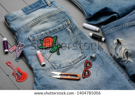Sewing embroidered patch to a favorite pair of jeans. Trendy denim refashion, new look for worn clothes.