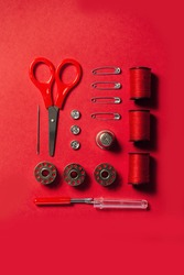 Sewing kit accessories and tools for needle work in red. Tape measure, pins, scissors, buttons, prewound bobbins, thimble, thread cutter flat lay. Knolling same color concept.