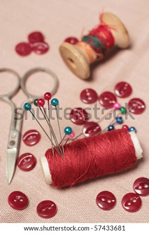 Sewing kit. Bobbins, scissors, buttons and pins. Focus is on the red bobbin with pins
