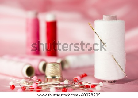 Sewing kit with cottons, pins and thimble in red and white - pink background.