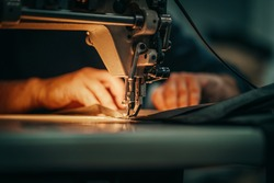 Sewing machine and men's hands of a tailor