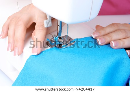 sewing machine, blue fabric and women's hands