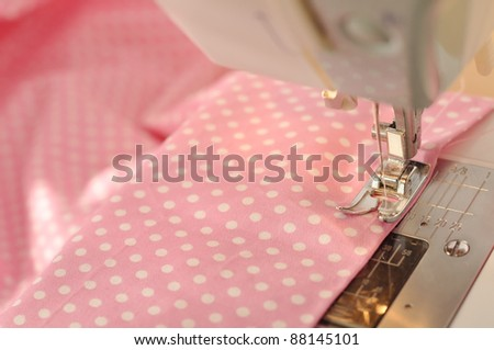 Sewing machine detail with the pink thread and fabric - stock photo