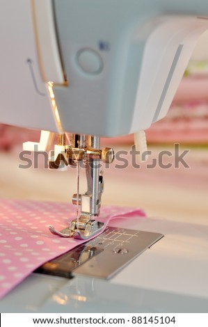 Sewing machine detail with the pink thread and fabric