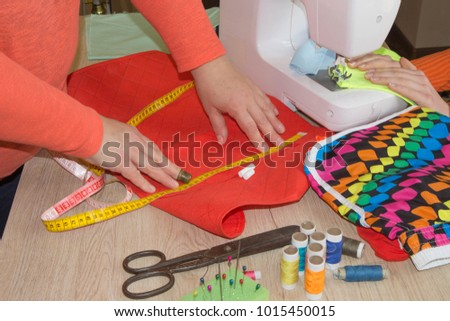 Sewing machine.sewing process in the phase of overstitching. Dressmaker work on the sewing machine. Tailor making a garment in workplace. Hobby sewing fabric as a small business concept #1015450015