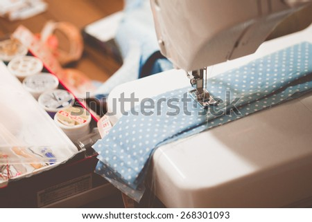 Sewing machine with many sewing utensils on a wooden table #268301093