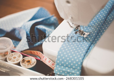 Sewing machine with many sewing utensils on a wooden table #268301105