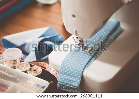 Sewing machine with many sewing utensils on a wooden table #268301111