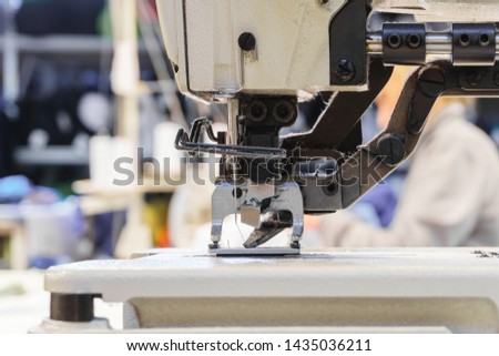 sewing mechanism of modern industrial overlock, covered with dust and pile