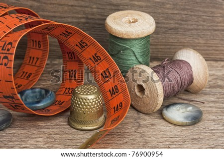 Sewing on the background of the old wooden walls