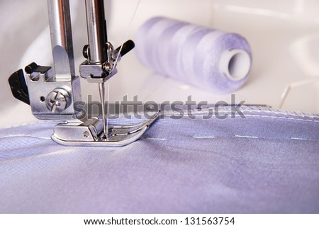 sewing process of blue cloth on the machine and two bobbins background