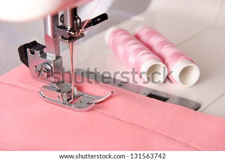 sewing process of rosy cloth on the machine and two bobbins background