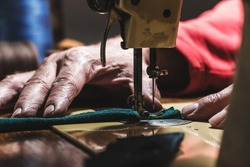 Sewing process of the leather belt. old Man's hands behind sewing. Leather workshop.