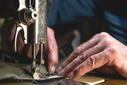 Sewing process of the leather belt. old Man's hands behind sewing. Leather workshop. textile vintage sewing industrial