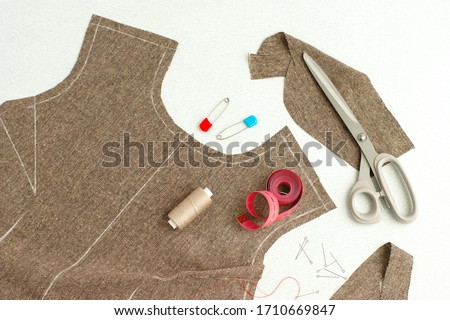 Sewing process. The process of sewing clothes on a white background. Cloth, tailoring scissors, needles, threads, centimeter tape on the table. Cut the dress according to the pattern. Foto stock ©