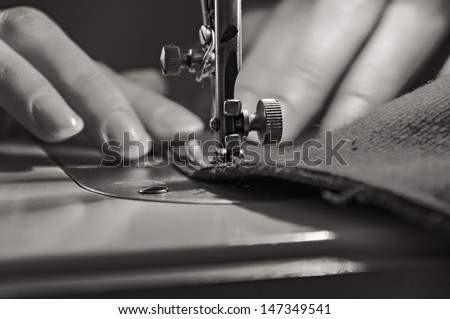 Sewing Process - Women's hands behind her sewing. Monochrome.