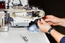 Sewing production, hands of the master repairing an industrial electric sewing machine. Copy space.