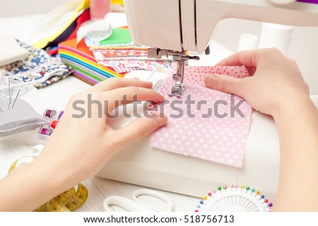sewing, sewing on the sewing machine, sewing supplies, colored sewing threads, colored pieces of cloth, needles, centimeter, tailors scissors on white wooden background #518756713