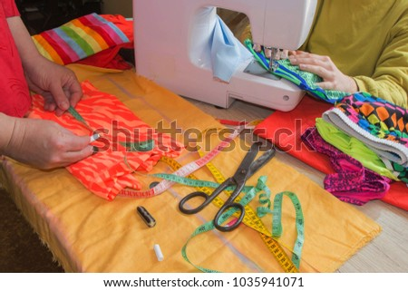 Sewing still life: colorful cloth. scissors and sewing kit includes threads of different colors, thimble and other sewing accessories on wooden table. tools for sewing for hobby #1035941071