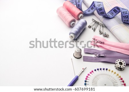 Sewing supplies and accessories for needlework. Fabric, spools of thread, scissors and thimbles on white background.