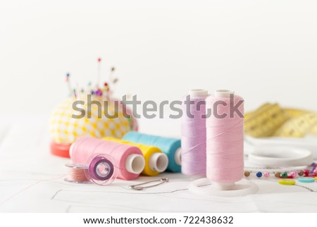 Sewing supplies on a white wooden table: sewing thread, scissors, a large spool of thread, pieces of cloth, needles,centimeter, buttons #722438632