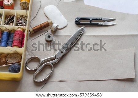 Sewing supplies - the attributes of the master. On the desktop lay a pair of scissors, a box of thread, needles and other tools of a seamstress. There is a free place for text. #579359458