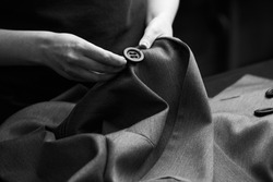 Sewing the buttons to the jacket. Tailor atelier - handmade exclusive clothes making and repair, private business, creative occupation concept