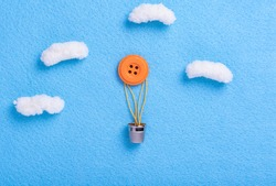 Sewing theme creative flat lay design: balloon with basket flying in the sky among clouds made of button, thread, thimble, fabrics
