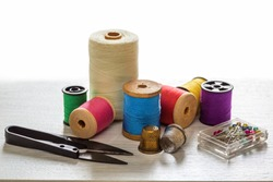 Sewing tools and accessories for sewing colored threads, coils, scissors, buttons, needles, pin and tailor meter on a white background Concept of sewing accessories.