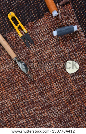 Sewing tools and sewing supplies accessories sewing on the brown fabric background with place for your text #1307784412