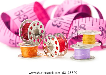 Sewing tools: bobbins with threads and measuring tape isolated on white