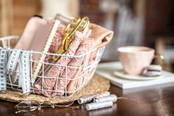Sewing tools of tailoring scissors, tape measure, coral coloured folded lace fabric in mesh basket on table near thread spools and eyeglasses. Concept of measurement for sewing evening ladies dress.