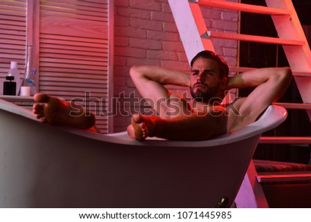 Sex and erotica concept. Macho sitting naked in bathtub with red lights on. Guy in bathroom with toiletries and stairs on background. Man with beard and dreamy face.  #1071445985