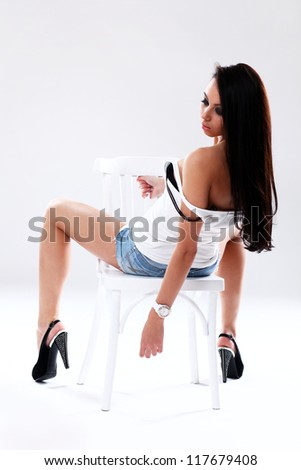 Sexual and seductive hot girl with long legs is stripping on a chair in studio