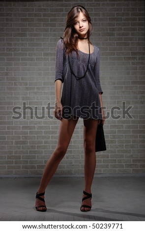 Sexual brunette fashion model  in knitted dress on brick wall background - stock photo