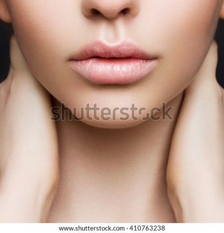 Sexual full lips. Natural gloss of lips and woman\'s skin. The mouth is closed. Increase in lips, cosmetology. Pink lips and long neck.