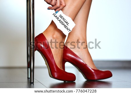 """Sexual harassment alert with young woman with red high heels shoes showing a note with the text """"sexual harassment"""" #776047228"""
