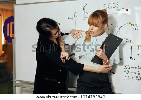 Sexual harassment and abuse at work. A female employee trying to push off her lady boss who's making inappropriate advances towards the young subordinate. The victim being frightened and disgusted.