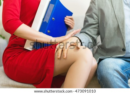 Sexual harassment at work. Man touching secretary's knee. #473091010