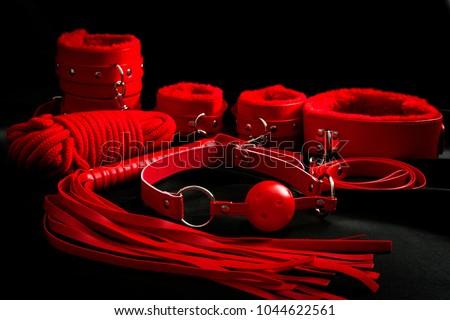 Sexual kink, erotic games and human sexuality concept with complete red sex toy kit set (ball gag, cuffs, rope, flogger, collar and leash) for BDSM fantasy play and bondge restraints on black silk - Shutterstock ID 1044622561