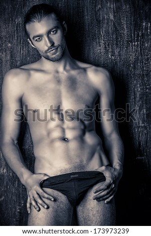 Sexual muscular nude man posing over dark background. Black-and-white photo.