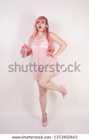 sexual plump redhaired girl wearing pink lingerie babydoll dress with headphones and having cosplay fun on white studio background
