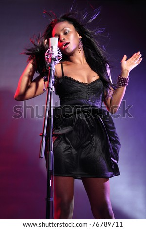 Sexy african american girl on stage with microphone singing, wearing a black dress and purple bead bracelet. Her hair is blowing back with wind effect and she is concentrating deeply on her song.