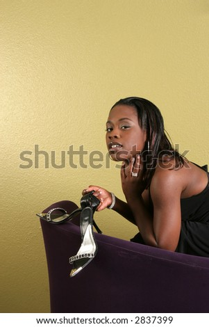 Sexy African American woman in a chair with a pair of fabulous stilettos swinging from her wrist